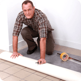 A workman laying vinyl flooring
