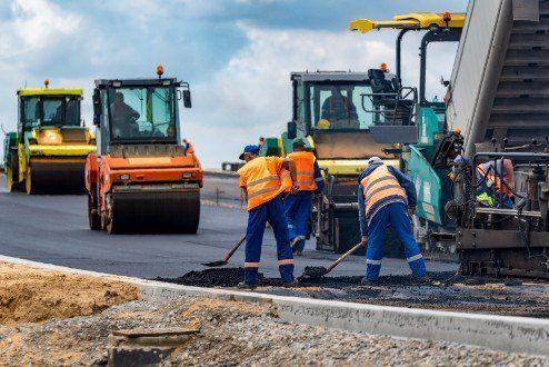 operai al lavoro sul asfalto