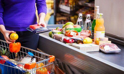 Una donna Mettendo i prodotti sul nastro per pagare