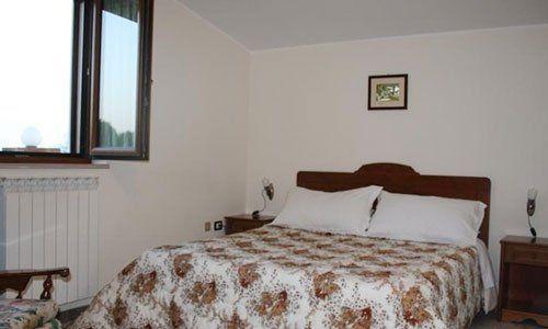 Una camera con un letto matrimoniale con due comodini e una poltrona davanti