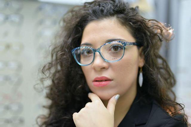 una ragazza con capelli ricci lunghi e occhiali da vista blu