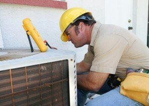 Man working on an AC unit on the top of a home