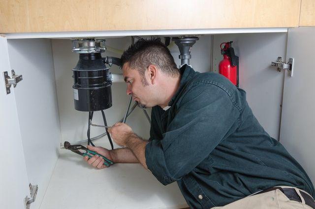 Professional plumber working on garbage disposal