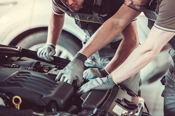Due meccanici regolando qualcosa nel motore della macchina