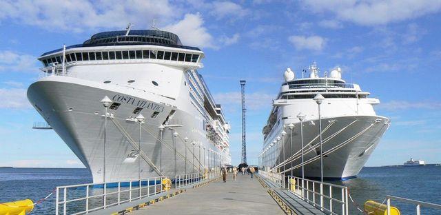 una lunga passerella sul mare e su entrambi i lati due navi da crociera color bianco e blu con scritto Costa Atlantica