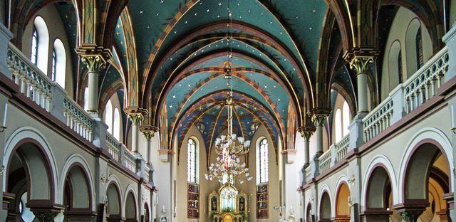 interno di una chiesa con grande lampadario al centro,colonne laterali e in fondo vista del Cristo e del tabernacolo
