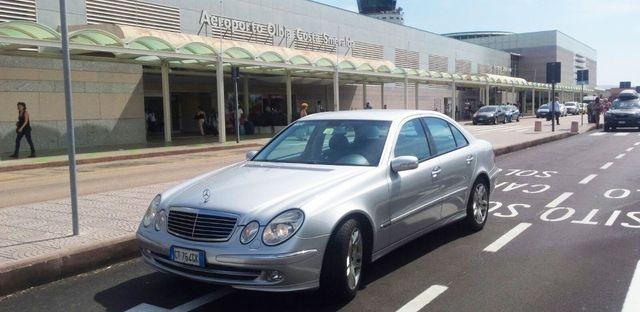 auto Mercedes Clk grigia metallizzata parcheggiata davanti all'entrata dell'aeroporto di Olbia, Costa Smeralda con persone che camminano e macchine parcheggiate
