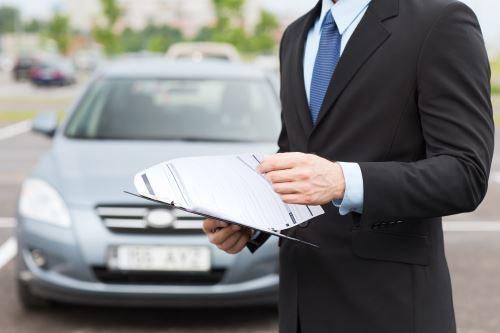 un uomo con un contratto e una macchina sullo sfondo