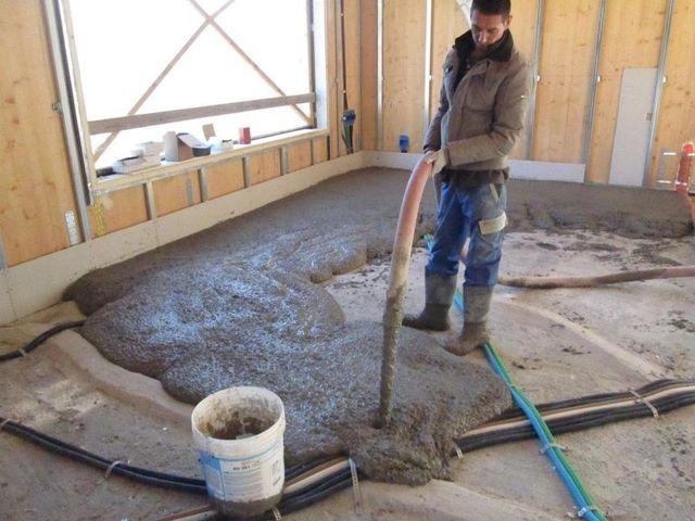 un uomo con degli stivali in gomma sta svuotando per terra del cemento con un tubo all'interno di uno stabile in costruzione