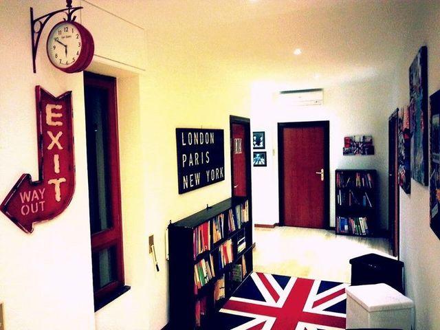 Corridoio con la bandiera inglese nel suolo, scaffali con libri e un orologio rosso di stazione nella parete