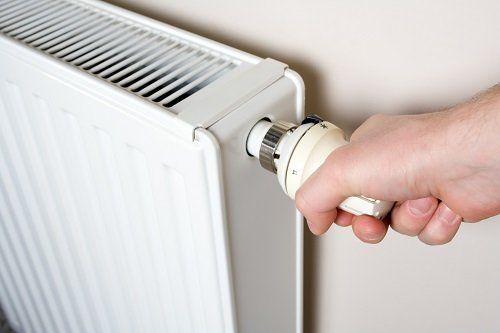una mano che regola un termosifone da una manopola