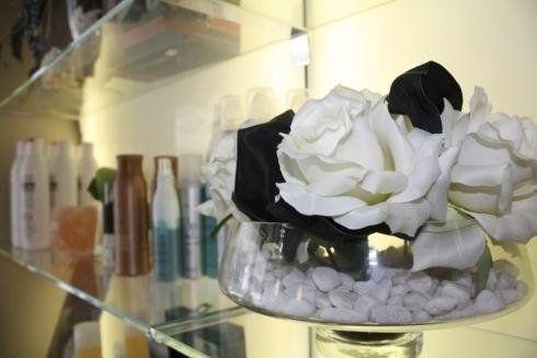 scaffale con assortimento prodotti e rose bianche dentro un vaso con ghiaia