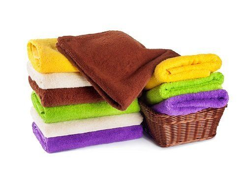 degli asciugamani piegati di diversi colori e un cesto