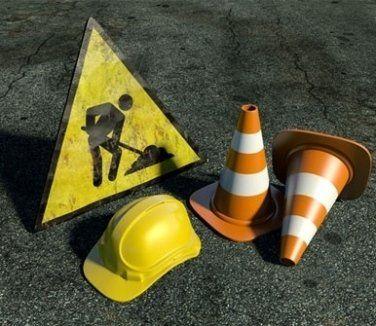 un cartello di lavori in corso, un elmetto e dei coni
