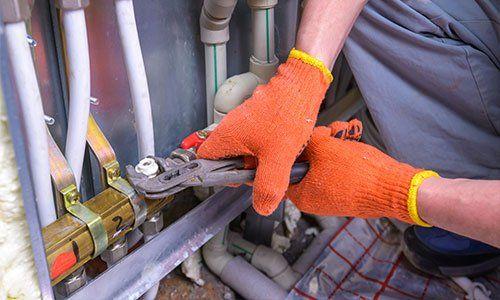 due mani con guanti arancioni stanno stringendo un bullone di una tubatura a Montesilvano