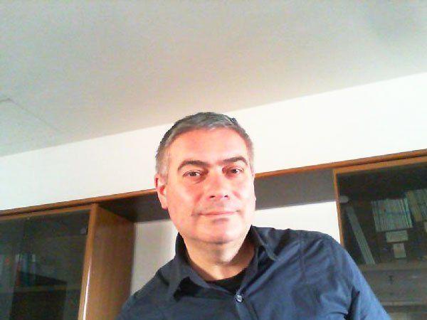 un uomo con capelli grigi, camicia blu  e dietro una libreria in legno