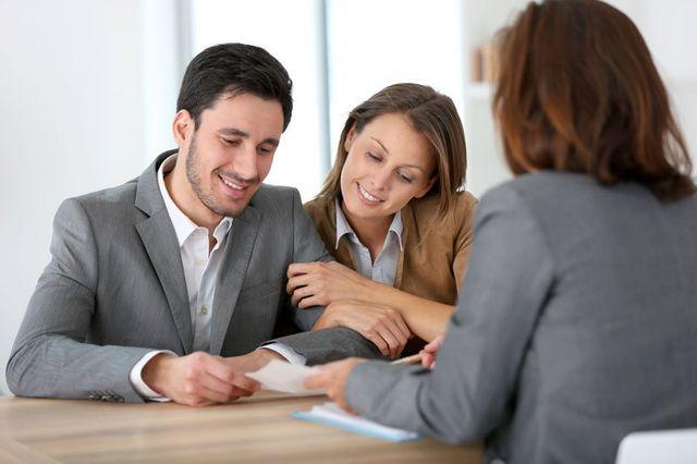 una coppia vestita elegante alla scrivania che guarda un foglio e dall'altra parte una donna che sta parlando con loro