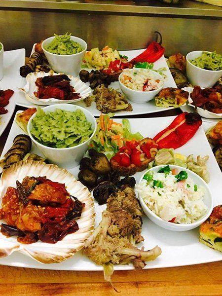 Piatto grande con ciotola di farfalle al pesto, insalata di riso, peperoni e melanzane dentro una conchiglia e una bruschetta a Catania, CT