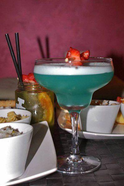Cocktail azzurro con fetta di fragola, cocktail servito in un barattolo di vetro, fetta di arancia e cannuccia a Catania, CT