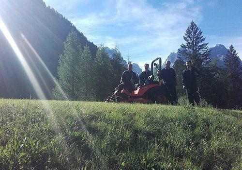 un taglia erba e quattro uomini accanto a un prato