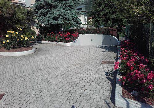 una pavimentazione esterna e delle auiole con delle rose di color giallo e rosso