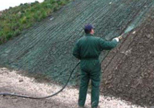 un uomo con una tuta verde e una canna d'acqua in mano