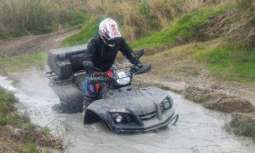 un ragazzo che guida un quad nel fango