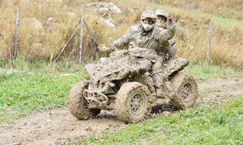 due persone su un quad sporco di fango