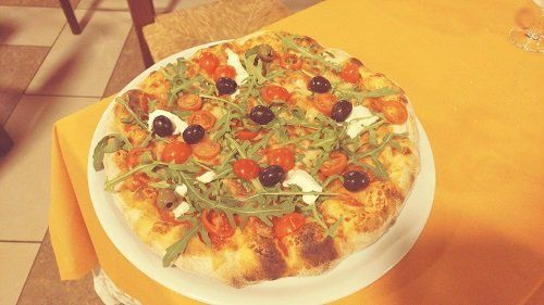 una pizza con rucola,pomodorini e olive nere