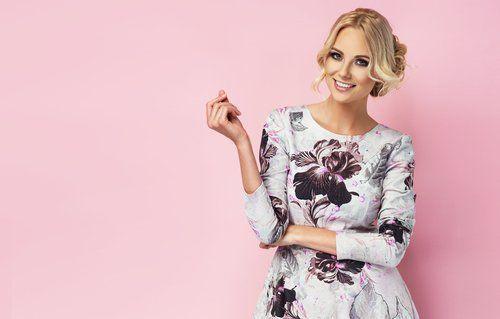 modella, su uno sfondo rosa, con un vestito che sorride