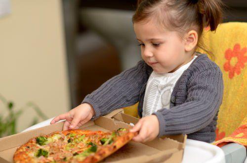 Bambina piccola  cogliendo la pizza