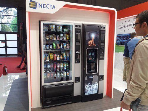 una persona davanti a un distributore automatico a marchio NECTA