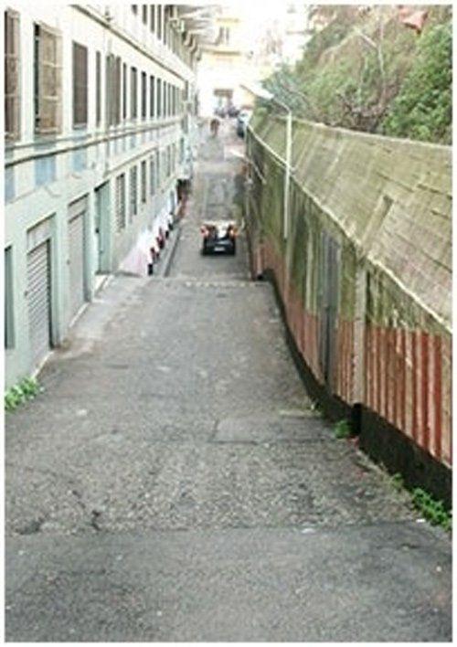 Una strada di paese in discesa con auto in sfondo