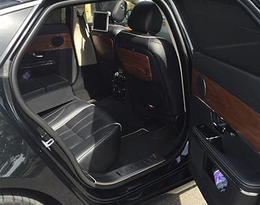 An open door with a view into a wood clad car interior