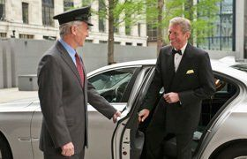 A chauffeur holding open a door for a man in a dinner suit