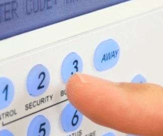vista di un dito che preme su dei tasti azzurri di un impianto anti intrusione
