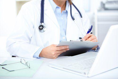Un medico scrive su una cartella clinica