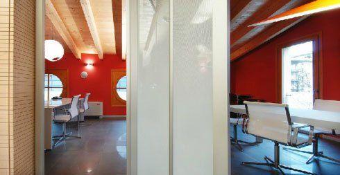 vista dal corridoio di due uffici, uno sulla destra e l'altro sulla sinistra con muri dipinti di rosso e sedie bianche