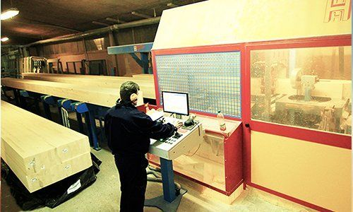 un uomo in una fabbrica che controlla un macchinario vicino a monitor