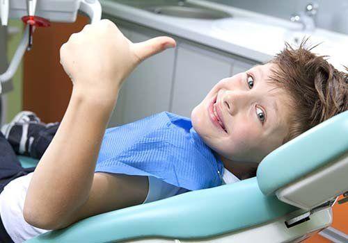 Bambino facendo un segnale di trionfo e sorridendo dalla poltrona della consultazione del dentista