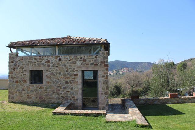 casetta in pietra ristrutturata con sfondo collinare