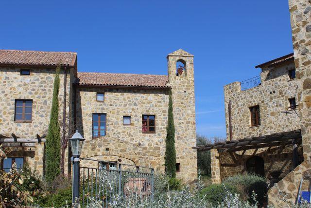 villa con torrretta in pietra e cipressi
