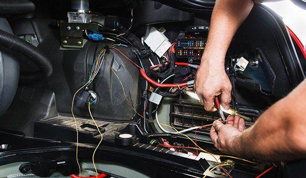 due mani che sono al lavoro su un impianto elettrico all'interno dell'abitacolo di una vettura