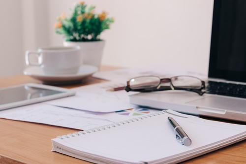 una scrivania d`ufficio con sopra un laptop e dei documenti