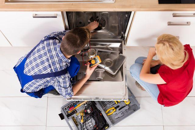 Tecnico aggiusta lavastoviglia con ragazza bionda