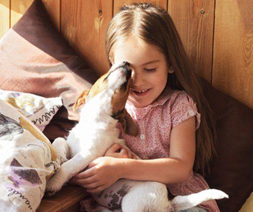 bambina gioca con un cane