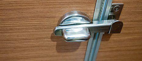 una maniglia cromata di una porta di legno