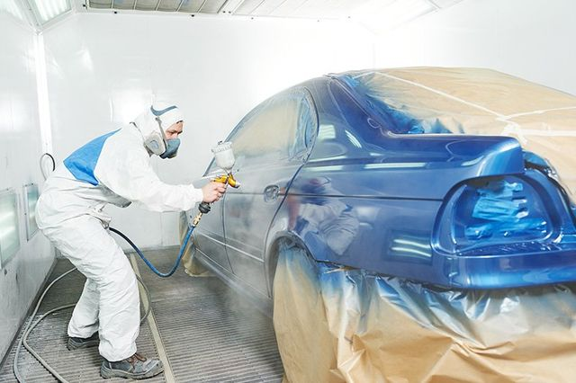 Painter applying paint to car body