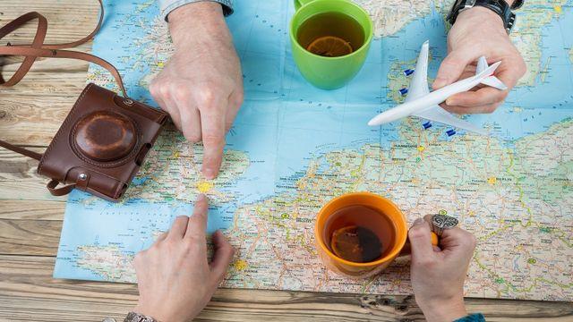 due dita che indicano una cartina geografica e delle tazze