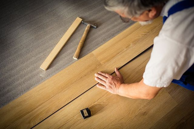 stretta di mano maschile che si trovano a bordo parquet / pavimenti in laminato